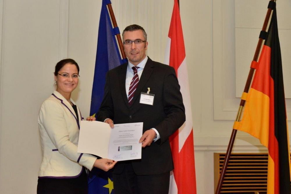 Claudia Buhl (VDI/VDE) übergibt die Urkunde zum Silberlabel an Cluster-Geschäftsführer Dr. Jürgen Bauer. Berlin, April 2016